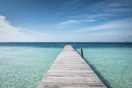 mujeres: wooden dock into blue tropical sea in Isla Mujeres, Mexico Yucatan