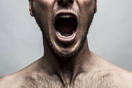 mouth close up: close up portrait of a man shouting, mouth wide open Stock Photo