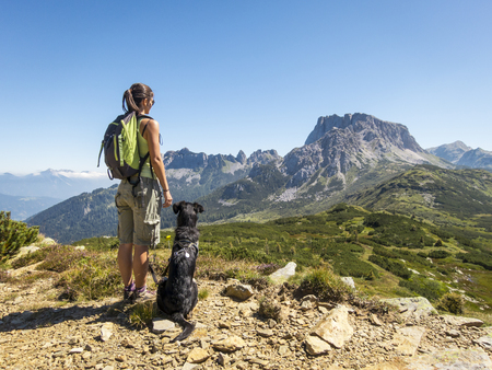 mountain valley: young beautiful woman enjoying the view with her dog during hiking trip in the mountain