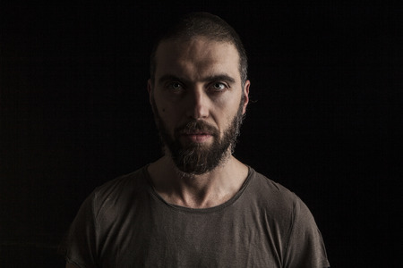 dark eyes: portrait of a handsome bearded man on dark background
