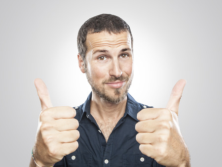 portrait of a smiling young man with thumbs up Stockfoto
