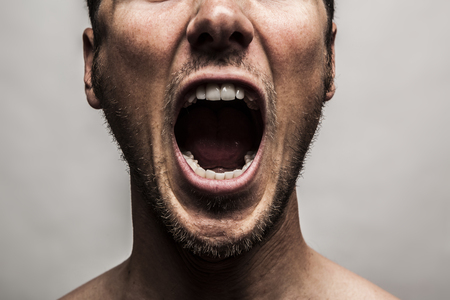 close up portrait of a man shouting, mouth wide open Stockfoto