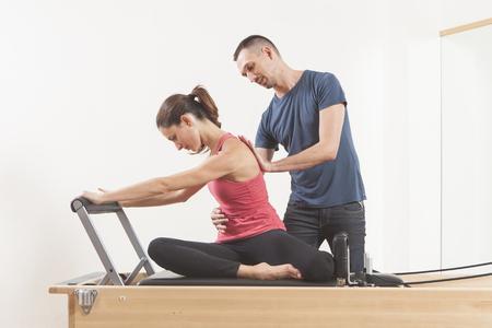 Lezione di Pilates sul riformatore, coaching personale giovane bella donna