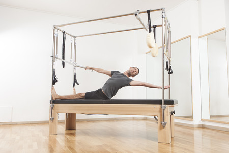 Pilates instructor performing fitness exercise on equipment, at the gym indoor