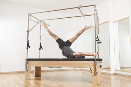 Pilates instructor performing fitness exercise on cadillac equipment, at the gym indoor Stock Photo