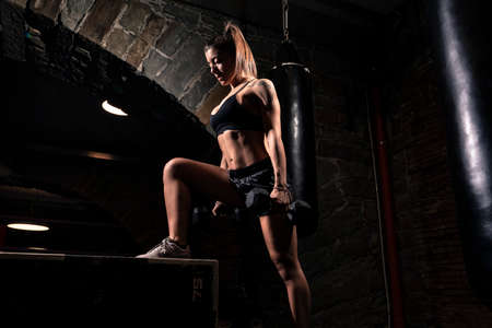 Strong fitness woman bodybuilder pumps up the muscles lifting in the gym. Stock fotó