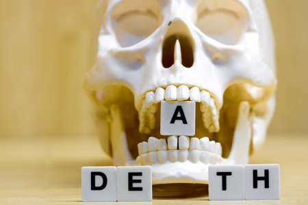 A row of small white plastic tiles, containing the letters forming the word death, placed on a table together with a skull, to represents the concept of death.