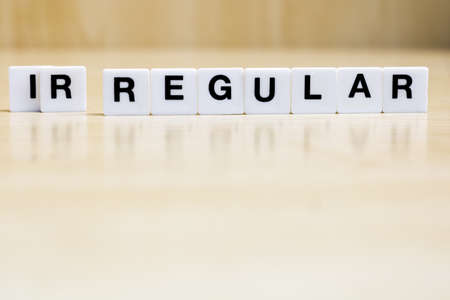 A row of small white plastic tiles, containing the letters forming the word regular, to it represents the concept of irregularity turning into something regular.