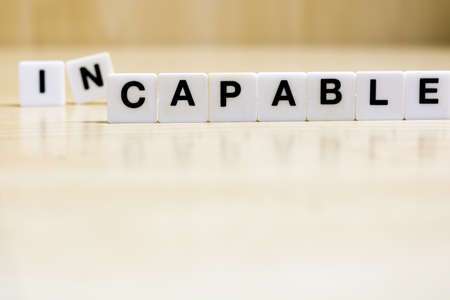 A row of small white plastic tiles, containing the letters forming the word capable, to represents the concept of acquiring competence and skills.