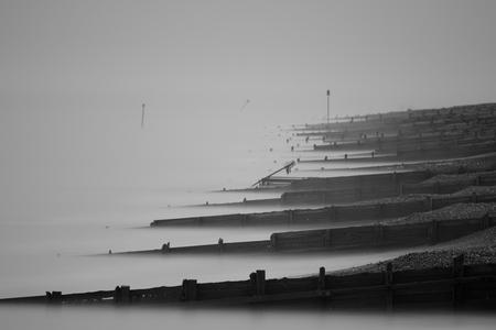 Black and white photo of the groynes on Worthing beach Standard-Bild - 113937577