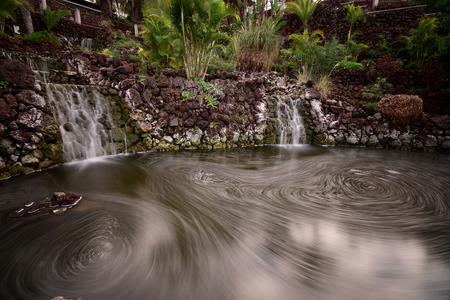 Long exposure of two waterfalls flowing into a pool of water in Parque Taoro in Puerto De La Cruz in Tenerife
