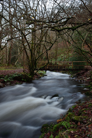 Long exposure of the river flowing under a wooden footbridge in Horner woods in Somerset Imagens - 120847710