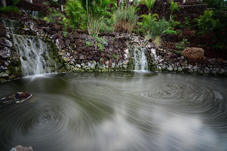 Long exposure of two waterfalls flowing into a pool of water in Parque Taoro in Puerto De La Cruz in Tenerife