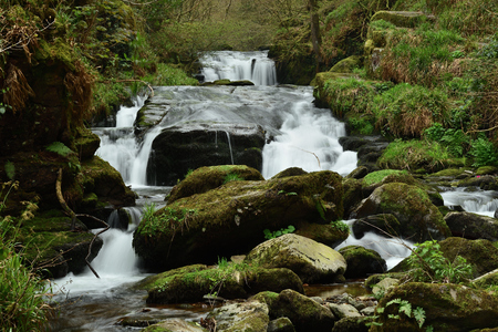 Long exposure of the big waterfall flowing through the forest at Watersmeet in Devon