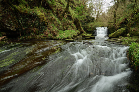 Long exposure of the big waterfall flowing through the woods at Watersmeet in Devon Imagens