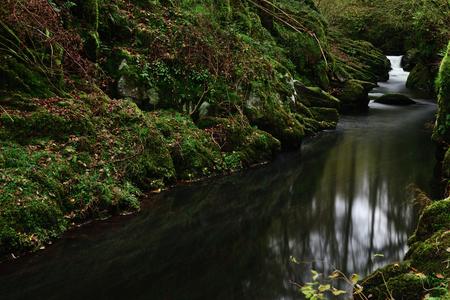 Long exposure of the river flowing through long pool at Watersmeet in Devon