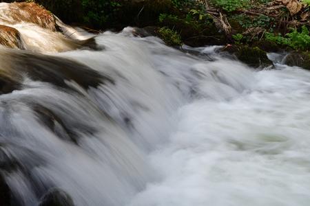 Long exposure of a waterfall flowing under a bridge