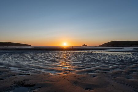 Landscape photo of the sun setting over Crantock beach in Cornwall 写真素材