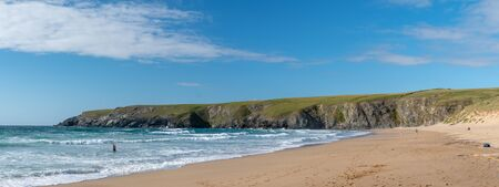 Panoramic photo of the beach and cliffs at Holywell bay in Cornwall