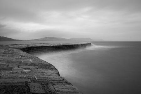Long exposure of Lyme Regis pier in Dorset in black and white 版權商用圖片