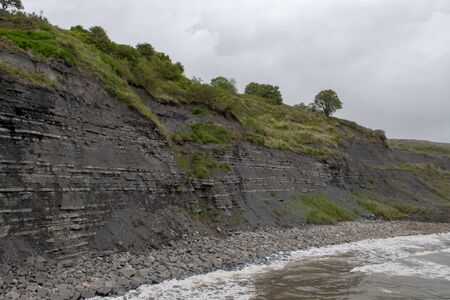 View of the blue lias cliff at Lyme Regis in Dorset which is famous for fossil hunting Banco de Imagens
