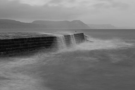 Long exposure of the waves crashing up against the Pier at Lyme Regis in Dorset in black and white