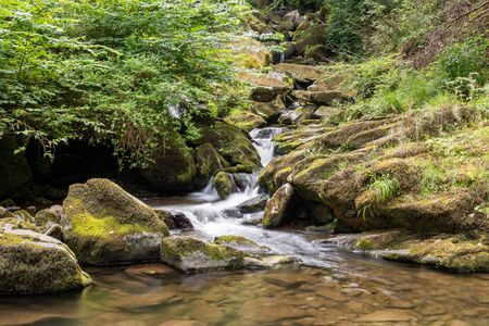 Long exposure of the West Lyn river flowing through the woods at Glen Lyn gorge at Lynmouth in Devon