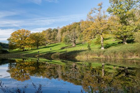 View of the autumn colours around the lake at Stourhead gardens in Wiltshire.