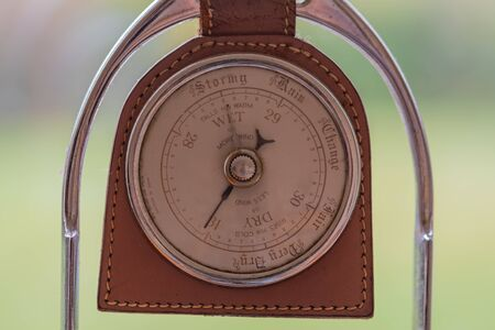 Close up of an old antique barometer made out of an old horses stirrup indicating high pressure and fine weather.
