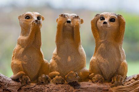Three ceramic meerkats depicting the proverb.Speak no evil.See no evil.Hear no evil. Banco de Imagens