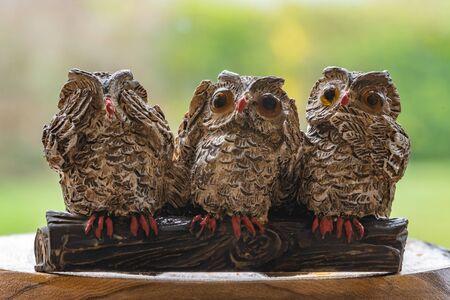 Close up of three ornamental owls depicting the proverb.See no evil.Hear no evil.Speak no evil.