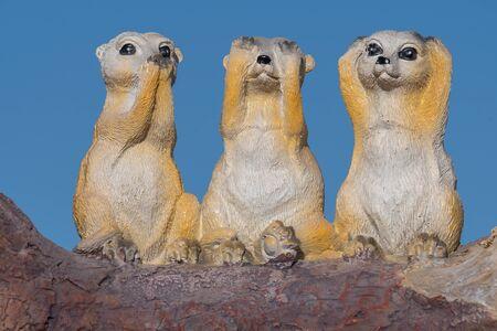 Close up of an ornament of three meerkats depicting the proverb hear no evil see no evil speak no evil.