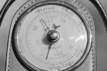 Close up of an antique barometer made out of an old horses stirrup indicating high pressure