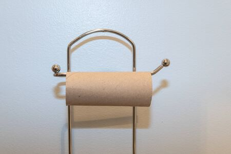 Close up of an empty toilet roll holder due to a shortage of toilet paper
