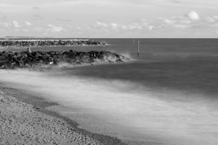 Long exposure of the tide flowing over rocks on the beach at West Bay in Dorset.