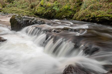 Long exposure of a waterfall on the East Lyn river at Watersmeet in Exmoor national park 写真素材