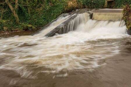 Long exposure of a waterfall on the river Avill in Dunster in Somerset