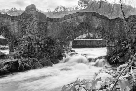Long exposure of a waterfall flowing under a bridge on the river Avill in Dunster