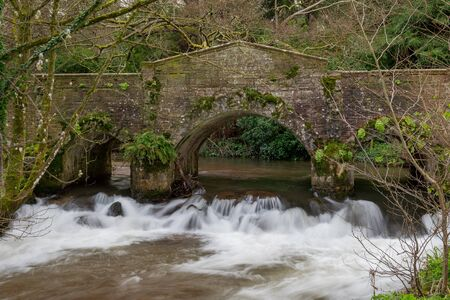 Long exposure of the River Avill flowing under a bridge in Dunster