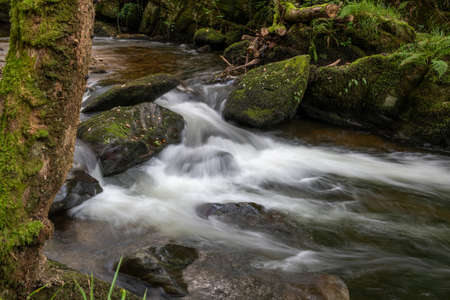 Long exposure of a waterfall on the East Lyn river flowing through the woods at Watersmeet in Exmoor National Park 写真素材
