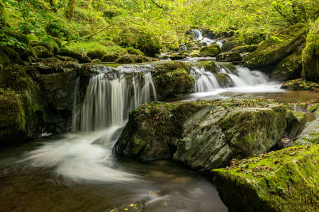 Long exposure of a waterfall on the Hoar Oak Water river flowing through the woods at Watersmeet in Exmoor National Park