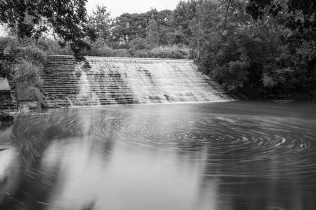 Long exposure of the River Brue flowing through the weir at West Lydford in Somerset