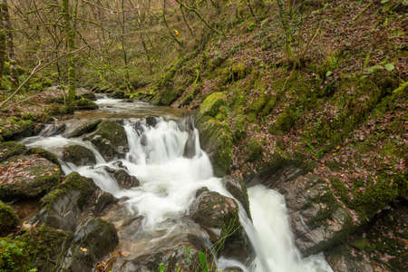 Long exposure of a waterfall on the Hoar Oak Water river at Watersmmet in Exmoor National Park in autumn