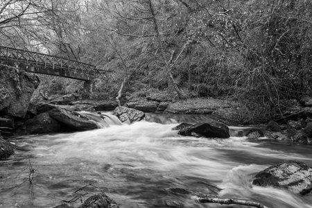 Long exposure of the East Lyn river flowing under a bridge at Watersmeet in Exmoor National Park