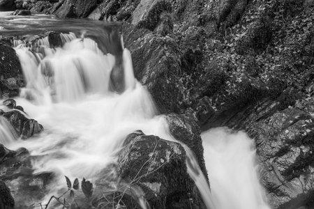 Long exposure of a waterfall on the Hoar Oak Water river at Watersmmet in Exmoor National Park in autumn