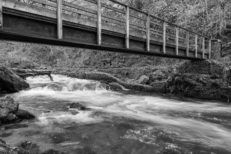 Long exposure of the East Lyn river flowing under Lynrock bridge at Watersmeet in Exmoor National Park 写真素材