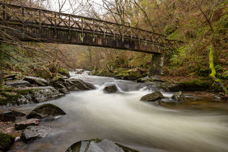 Long exposure of the East Lyn river flowing under a bridge at Watersmeet in Exmoor National Park in autumn