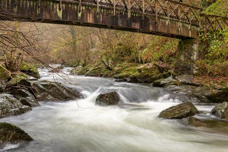 Long exposure of the East Lyn river flowing under a bridge at Watersmeet in Exmoor National Park in autumn