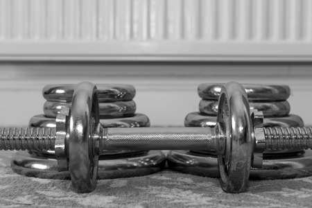 Black and white photo of a small dumbbell on the floor with two stacks of weights behind it