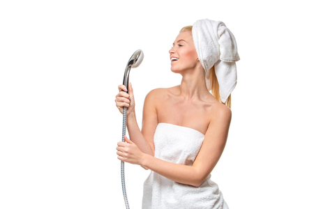 Gelukkige mooie vrouw in handdoek zingen met behulp van douchekop plezier, geïsoleerd op wit.
